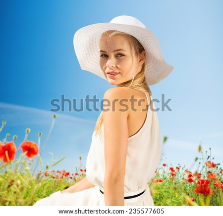 happiness, nature, summer, vacation and people concept - smiling young woman with closed eyes wearing straw hat on poppy field - stock photo