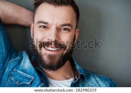 Happiness never goes out of style. Cheerful young man holding hand behind head and smiling at camera while standing against grey background - stock photo