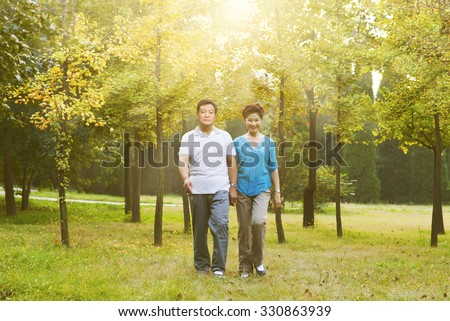 Happiness of the elderly seniors picking for a walk in the park - stock photo