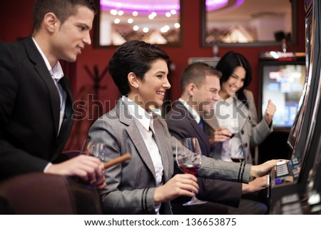 Happiness people gambling in the casino on slot machines - stock photo