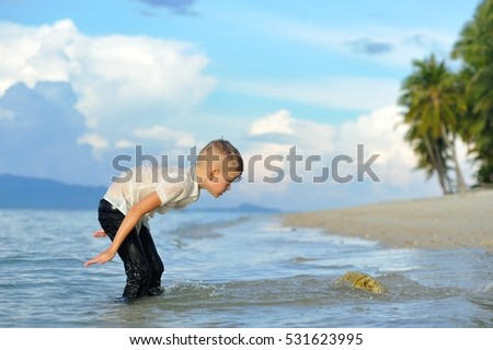 Happiness portrait in tropical water: cute and elegant 8 years old boy in wet shadeless bright slim fit shirt and dark pants standing in the sea water, happily making splashes