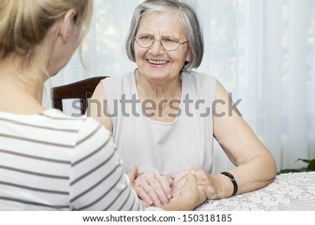 Happiness senior woman  holding hands with her mature daughter. - stock photo