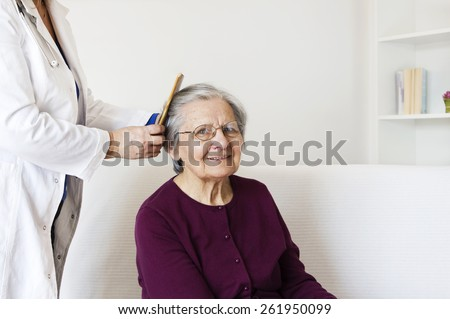 Happiness senior woman sitting on the sofa  at home  looking at camera and enjoying while the  mature nurse  combing her gray hair.  - stock photo