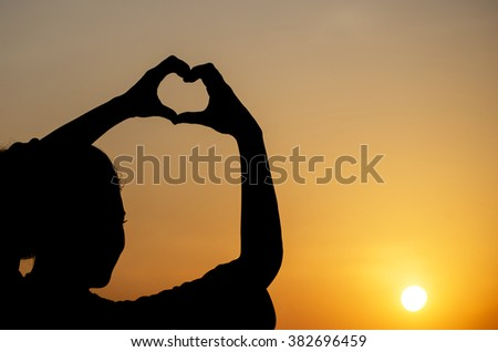 happiness silhouette woman making heart shape - stock photo