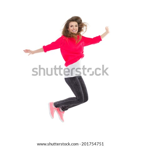 Happiness. Smiling girl jumping with arms outstretched. Full length studio shot isolated on white.