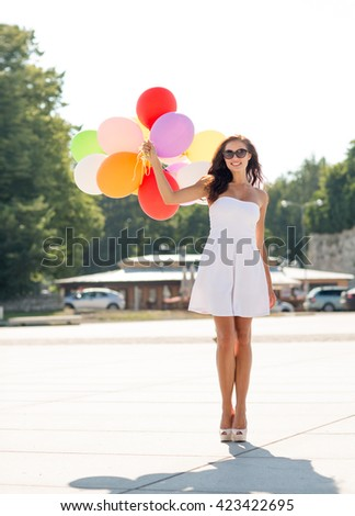 happiness, summer, holidays and people concept - smiling young woman wearing sunglasses with balloons in park - stock photo