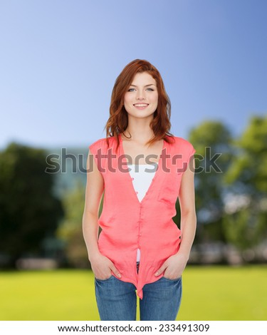 happiness, summer vacation and people concept - smiling teenage girl in casual clothes over park background - stock photo