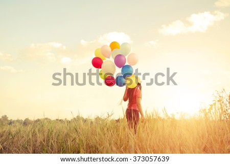 Happiness teen girl with colorful balloons enjoy in the sundown time at grassland. Happy birthday party. vintage color tone effect - stock photo