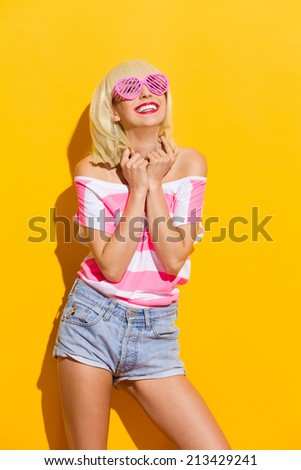 Happiness through pink glasses. Beautiful blond girl in pink sunglasses smiling. Three quarter length studio shot on yellow background.