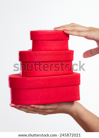 Happiness, valentines day love and celebrating concept. Closeup red heart-shaped gift boxes in female hands on white - stock photo