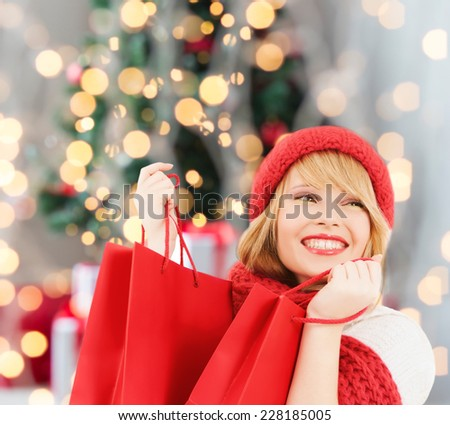 happiness, winter holidays and people concept - smiling young woman in hat and scarf with red shopping bags over christmas tree background