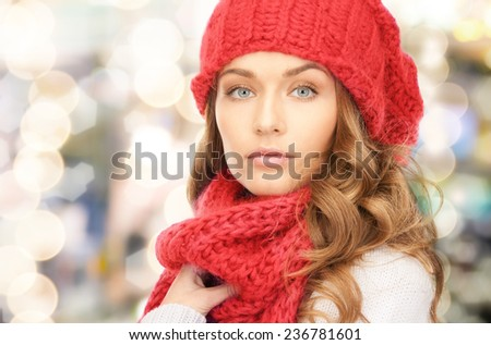 happiness, winter holidays, christmas and people concept - close up of young woman in red hat and scarf over lights background - stock photo