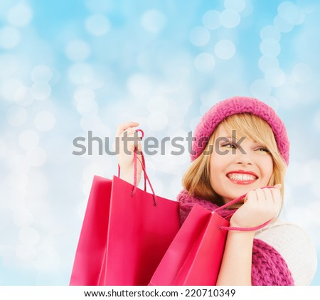 happiness, winter holidays, christmas and people concept - smiling young woman in hat and scarf with pink shopping bags over blue lights background
