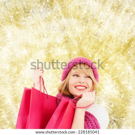 happiness, winter holidays, christmas and people concept - smiling young woman in hat and scarf with pink shopping bags over yellow lights background - stock photo