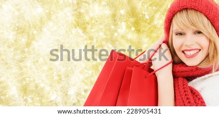 happiness, winter holidays, christmas and people concept - smiling young woman in hat and scarf with red shopping bags over yellow lights background - stock photo