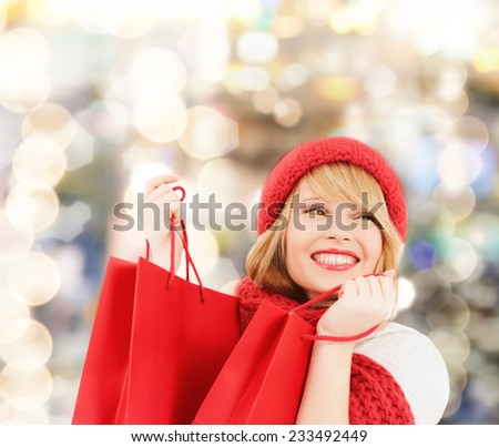happiness, winter holidays, christmas and people concept - smiling young woman in hat and scarf with red shopping bags over lights background
