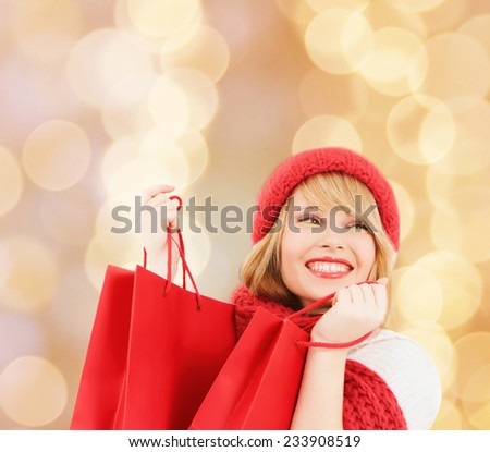 happiness, winter holidays, christmas and people concept - smiling young woman in hat and scarf with red shopping bags over beige lights background - stock photo