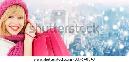 happiness, winter holidays, christmas and people concept - smiling young woman in hat and scarf with pink shopping bags ove snowy city background - stock photo