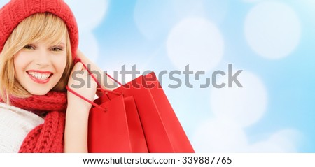 happiness, winter holidays, christmas and people concept - smiling young woman in hat and scarf with shopping bags over blue lights background - stock photo