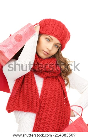 happiness, winter holidays, christmas and people concept - smiling young woman in red hat, scarf and mittens carrying shopping bags over white background
