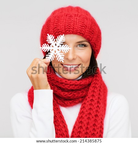 happiness, winter holidays, christmas and people concept - smiling young woman in red hat, scarf and mittens covering one eye with snowflake decoration over gray background