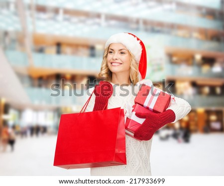 happiness, winter holidays, christmas and people concept - smiling young woman in santa helper hat with gift boxes and shopping bag over shopping center background - stock photo