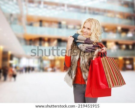 happiness, winter holidays, christmas and people concept - smiling young woman in winter clothes with red bags over shopping center background - stock photo