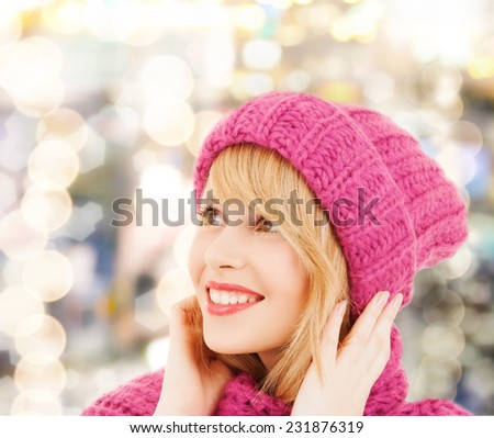 happiness, winter holidays, christmas and people concept - young woman in pink hat and scarf over lights background - stock photo