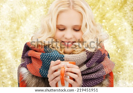 happiness, winter holidays, christmas, beverages and people concept - smiling young woman in warm clothes with cup over yellow lights background - stock photo