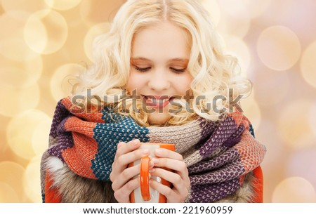 happiness, winter holidays, christmas, beverages and people concept - smiling young woman in warm clothes with cup over blue lights background - stock photo