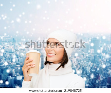 happiness, winter holidays, christmas, beverages and people concept - smiling young woman in white hat and mittens with coffee cup over snowy city background