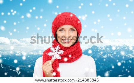 happiness, winter holidays, tourism, travel and people concept - smiling young woman in red hat and mittens holding snowflake over snowy mountains background