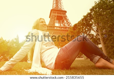Happiness Woman seating on the grass in Paris under sunlight - stock photo