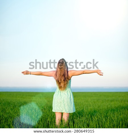 Happiness woman stay outdoor under sunlight of sunset. With raised hands at the sunrise time.