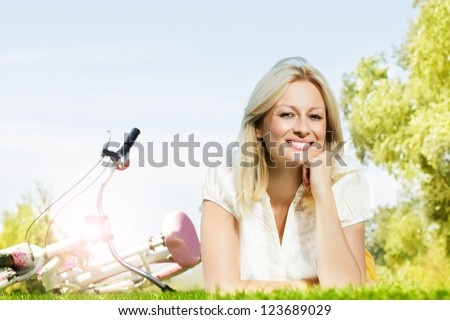 Happiness young blond woman relaxing on green grass at beautiful summer day.