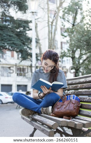 Happiness young woman sitting on old wood bench and reading book, outdoor. - stock photo