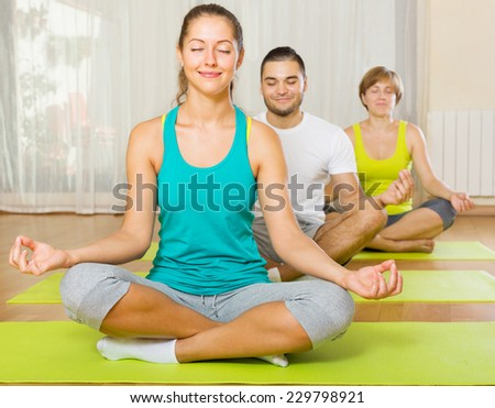 happy active adults at group yoga practice in fitness club - stock photo