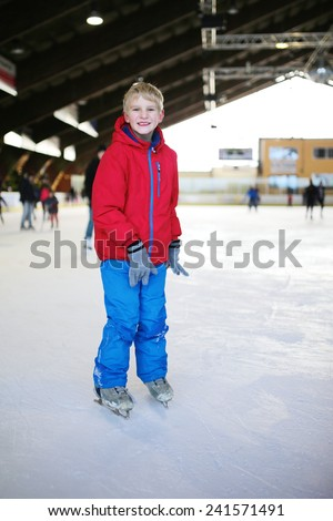 Happy active child, blonde caucasian teenage boy, wearing colorful snowsuit, having fun at indoors skating rink - wintertime fun concept - stock photo