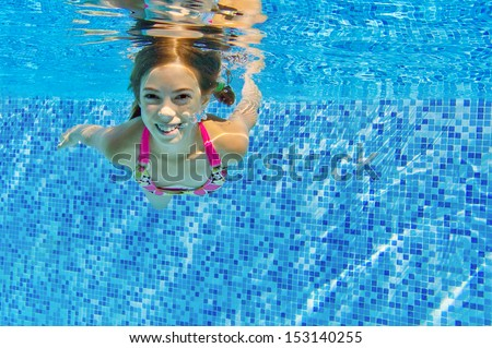 Happy active child swims underwater in pool, beautiful healthy girl swimming and having fun on family summer vacation, kids sport concept  - stock photo