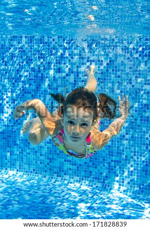 Happy active child swims underwater in pool, beautiful healthy girl swimming and having fun on family summer vacation, kids sport concept, vertical image  - stock photo