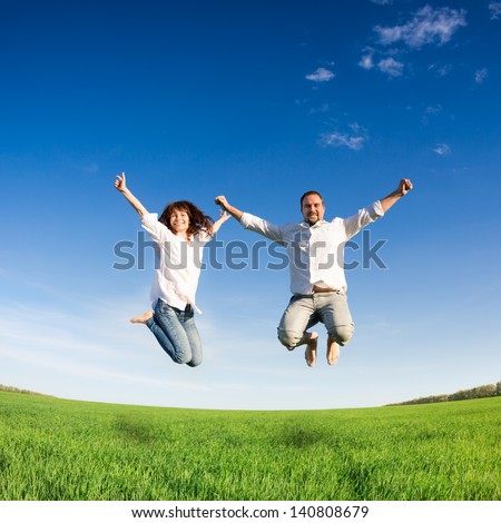 Happy active couple jumping in green field against blue sky. Summer vacation concept - stock photo