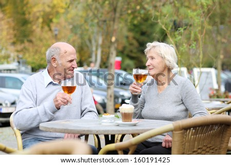 Happy active couple of seniors, a man and his wife, are enjoying glass of cold beer sitting at the open air terrace of cozy cafe in the city center on a warm sunny day