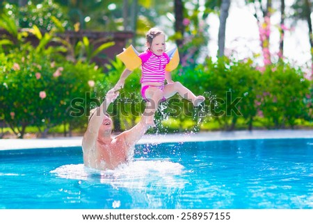 Happy active family, young father and his cute daughter, adorable toddler girl, playing in a swimming pool jumping into the water enjoying summer vacation in a beautiful tropical island resort - stock photo