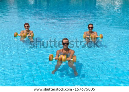 Happy active fitness people doing exercise with aqua dumbbell  - stock photo