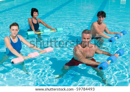 Happy active fitness people doing exercise with aqua dumbbell in a swimming pool - stock photo