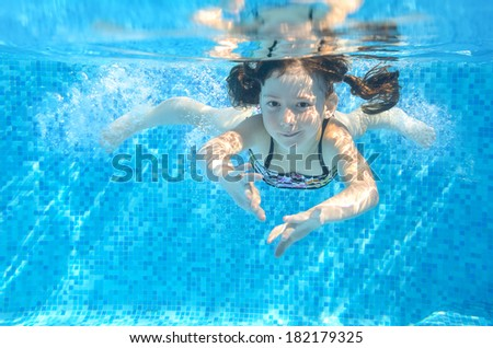 Happy active girl swims underwater in pool, beautiful healthy child swimming and having fun on family summer vacation, kids sport concept