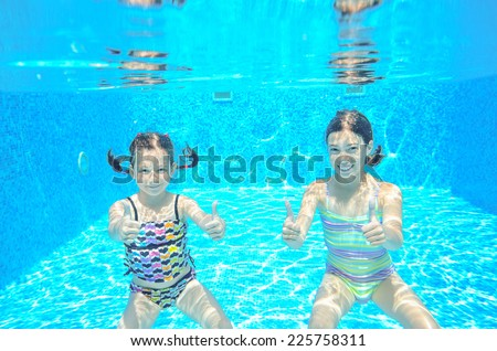 Happy active kids swim in pool and play underwater, girls diving and having fun, children on summer  vacation, sport concept  - stock photo