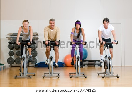 Happy active people exercising with bicycles in a gym. Front view - stock photo