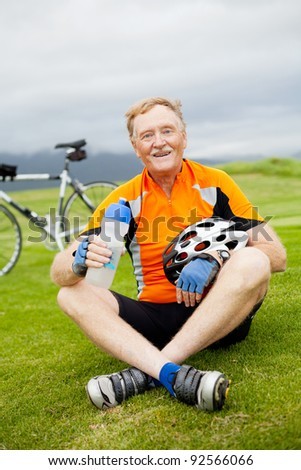 happy active senior bicyclist sitting on grass and resting