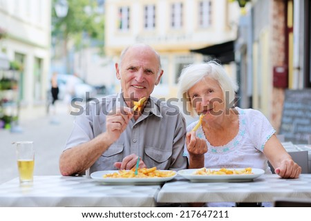 Happy active senior couple enjoying time together eating belgian french fries in outdoors street cafe on a summer day in typical European town - active retirement concept - stock photo